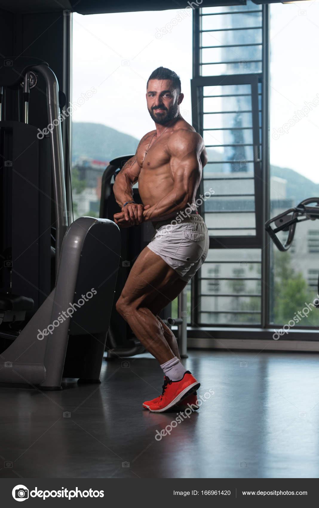 Jeunes en santé tatouent homme debout fort dans la salle de sport et des  Muscles de flexion - musculaire Bodybuilder Athletic Fitness modèle posant  après ... b87fcc377ae