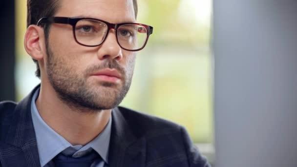 pohledný podnikatel v obleku a brýlích