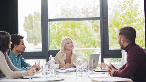 confident, smiling businesswoman talking with multicultural colleagues