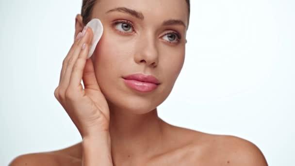 žena čištění obličeje a úsměv na kameru izolované na bílém