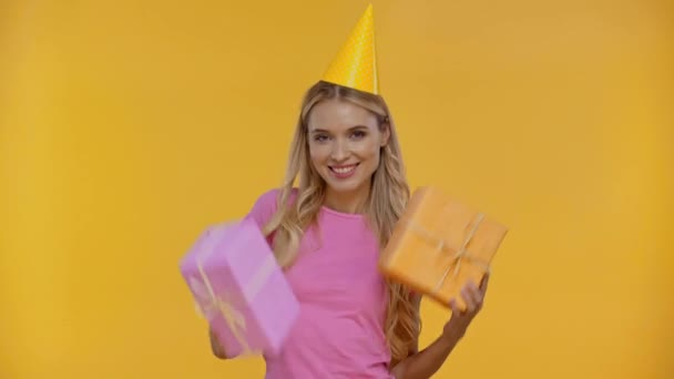 smiling woman dancing with gifts isolated in yellow