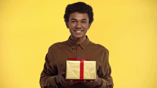afro-amerikai tinédzser kezében ajándék elszigetelt sárga