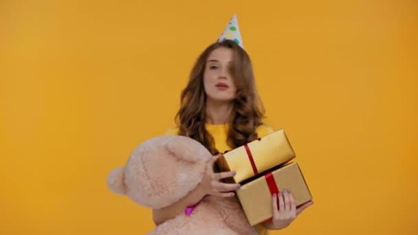 nő táncol ajándékokkal és plüssmackó elszigetelt sárga