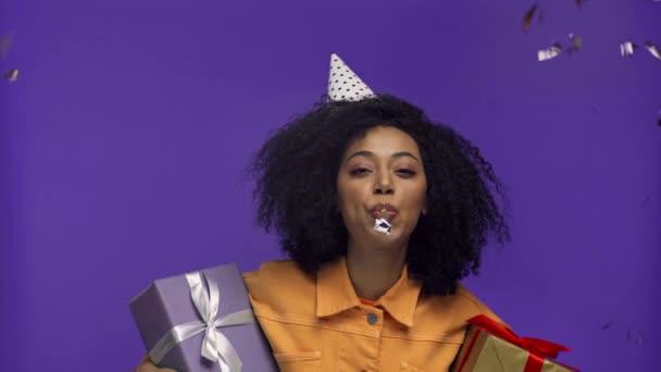 Afričanky americká žena foukání v strana rohu izolované na fialové