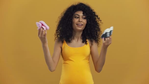 happy bi-racial pregnant woman showing baby booties isolated on dark yellow