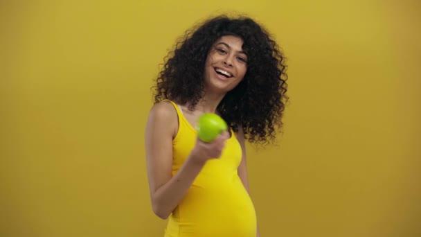 šťastný bi-rasové těhotné žena drží zralé jablko izolované na tmavě žluté