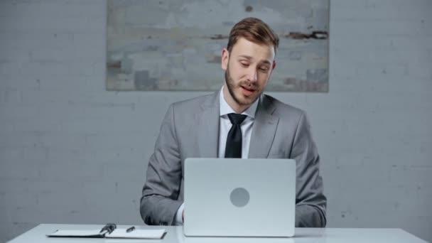 confident businessman having video call on laptop