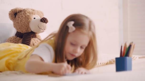 Szelektív fókusz a játékmackó által gyerek rajz az ágyra