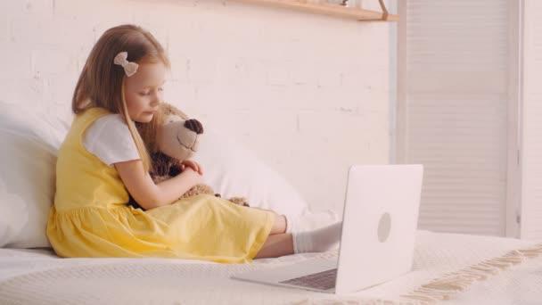 Gyerek játékmackó néz rajzfilmeket laptop és ásít az ágyban