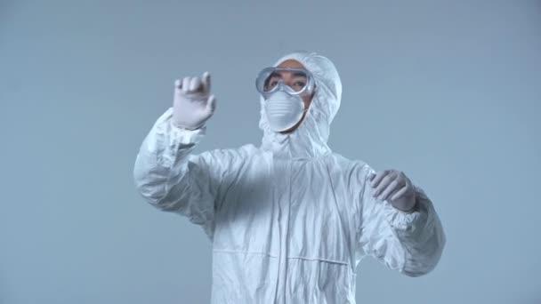 asiatischer Wissenschaftler im Schutzanzug gestikuliert isoliert auf grau