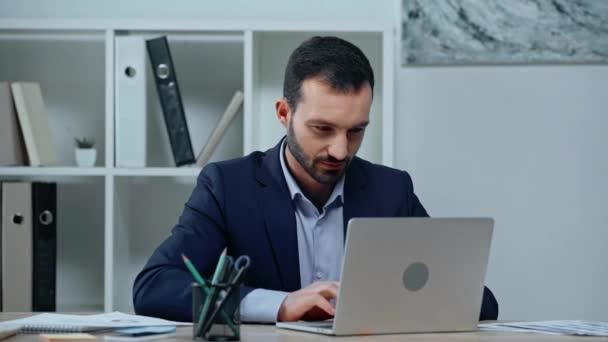 veselý podnikatel psaní na notebook a usmívá se na kameru