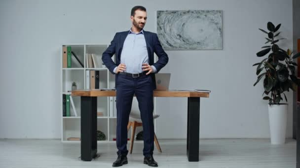 handsome businessman exercising while standing near workplace in office
