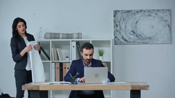 businesswoman taking fitness mat and towel while colleague sitting at workplace