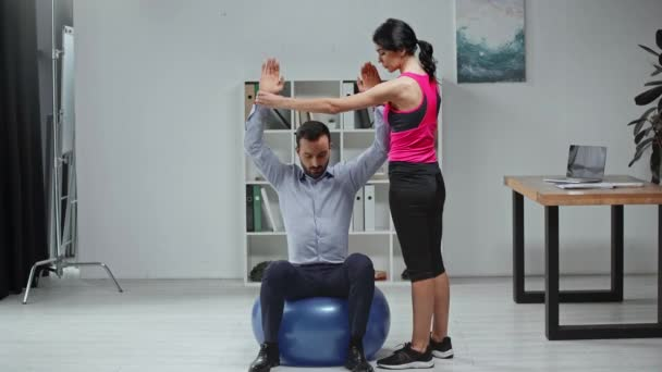 young fitness trainer helping businessman exercising on fitness ball in office