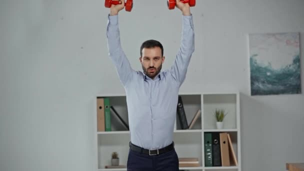 handsome businessman exercising with dumbbells in office