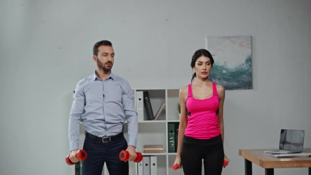 attractive fitness trainer and businessman exercising with dumbbells in office
