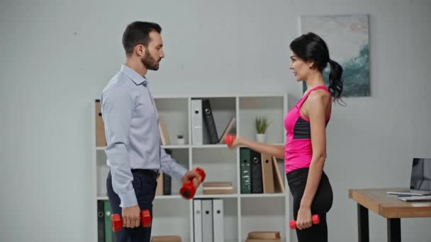 fitness trainer showing to businessman how to exercise with dumbbells