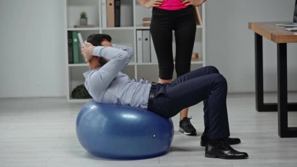 cropped view of fitness trainer near businessman doing abs on fitness ball