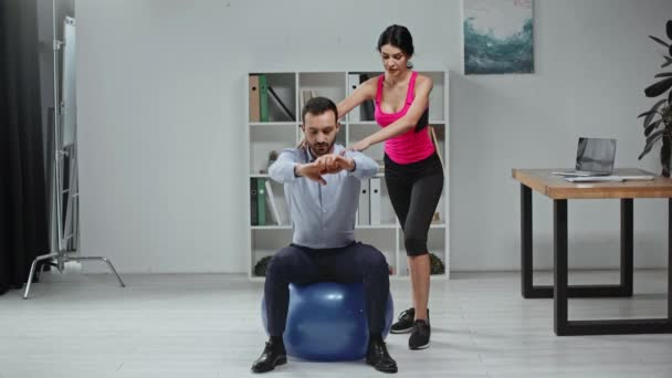 young trainer helping businessman with doing sit ups on fitness ball in office