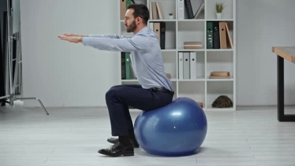 side view of businessman in formal wear doing sit ups on fitness ball in office