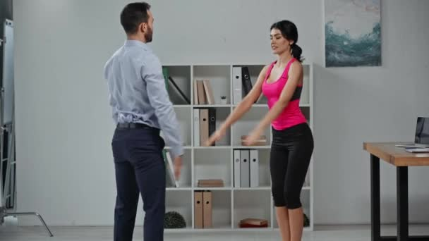attractive fitness trainer and businessman exercising in office together