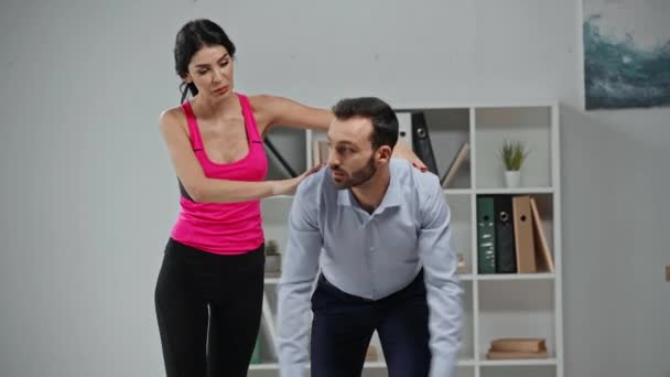 attractive fitness instructor training businessman doing exercising in office