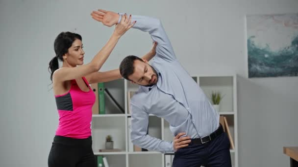 attractive fitness trainer instructing businessman doing exercising in office