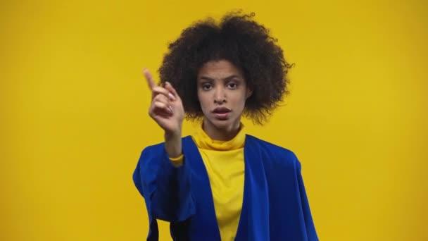 Afričanky americká žena ukazuje palce dolů izolované na žluté