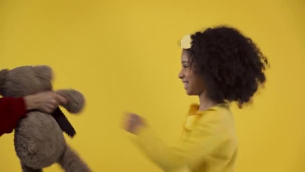 african american kid fighting with teddy bear isolated on yellow