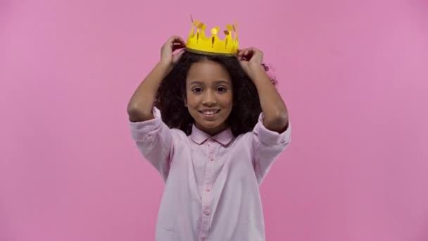 african american kid wearing cardboard crown isolated on pink