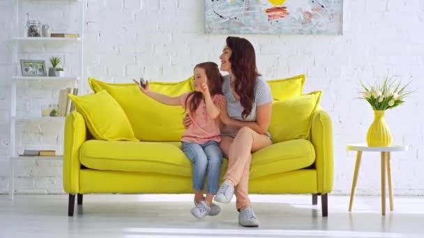 šťastná matka a dcera se selfie v obývacím pokoji