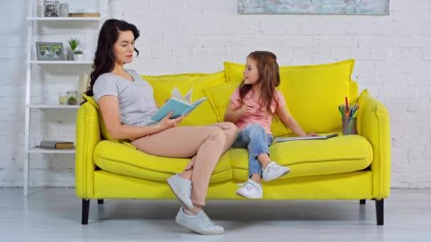 dítě ukazující kresbu šťastné matce v obývacím pokoji