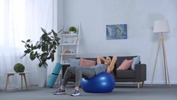 Usmívající se sportovkyně dělá břišní svaly na fitness míč v obývacím pokoji