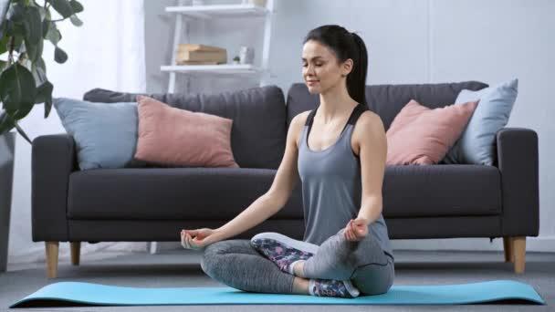 Usmívající se žena medituje na fitness podložku doma