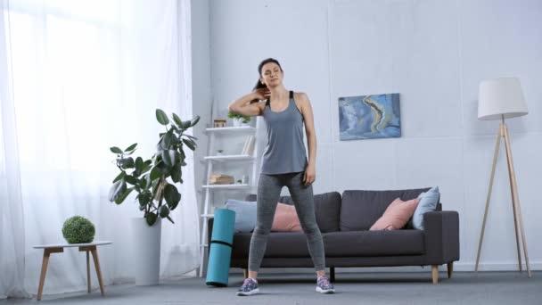 Krásná sportovkyně zahřívání v obývacím pokoji