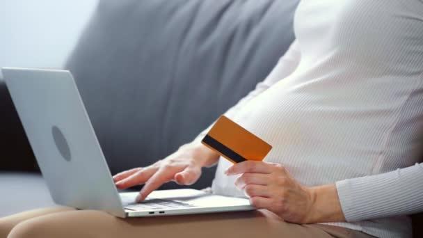 Vágott kilátás terhes nő laptoppal és hitelkártyával a kanapén