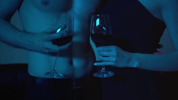 Ausgeschnittene Ansicht eines hemdlosen Mannes und einer Frau, die Gläser mit Wein auf Blau halten