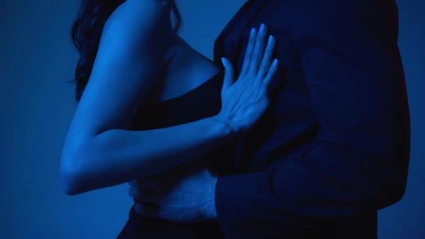 leidenschaftliche Frau berührt Mann im Blazer auf Blau