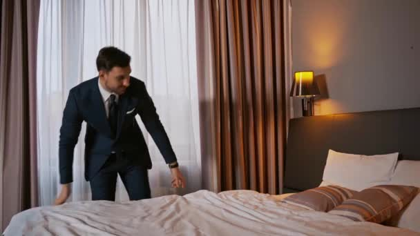 businessman in suit touching blanket on bed in hotel