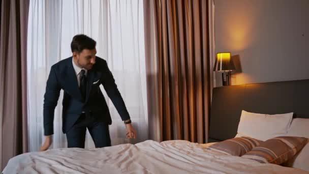 obchodník v obleku dotýkající se přikrývky na posteli v hotelu