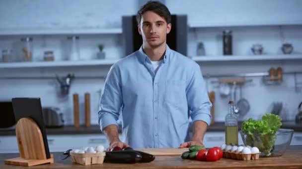 usmívající se muž při pohledu do kamery, zatímco stojí u stolu s čerstvými ingrediencemi
