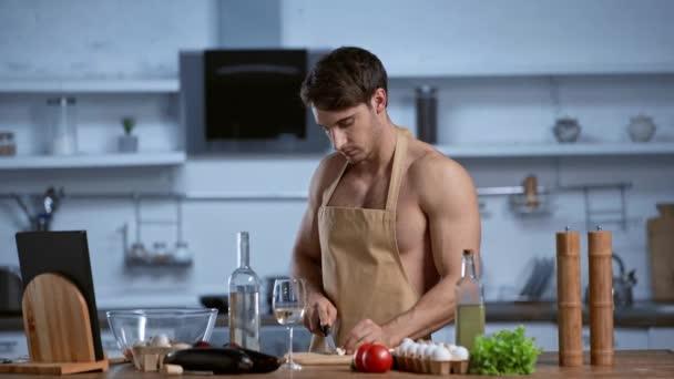 Hemdloser Mann in Schürze kocht in der Küche, blickt in die Kamera und lächelt