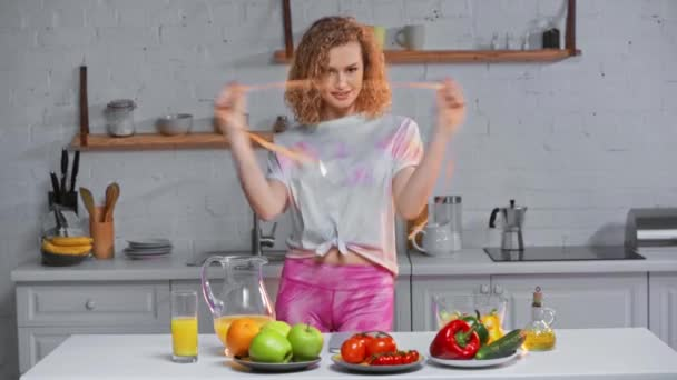 Sad woman measuring waist near fruits and vegetables on table
