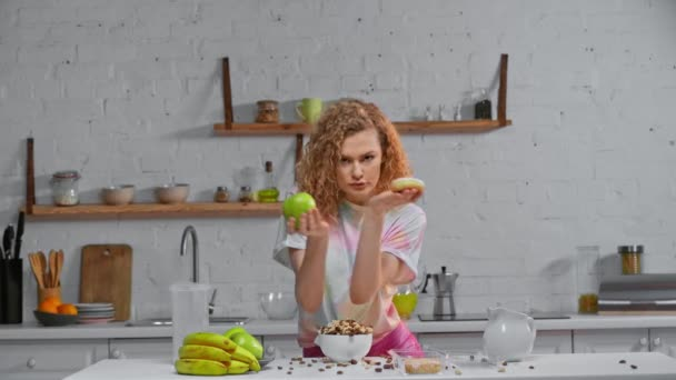 Woman dancing with apple and doughnut near cereals on table