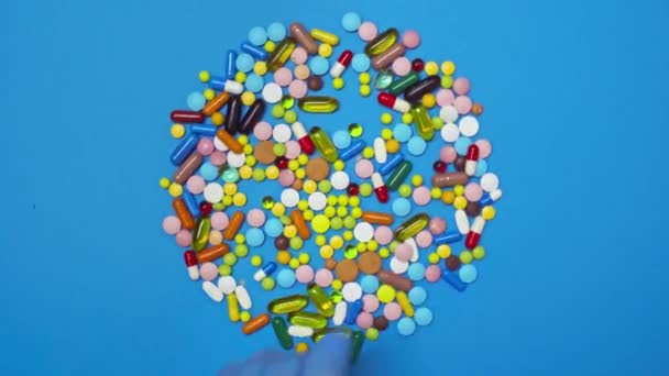 Top view of doctor putting pills on spinning blue background