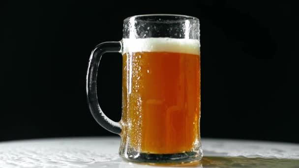oříznutý pohled na muže, jak dává hrnek se světlým pivem na bílý stůl izolovaný na černém