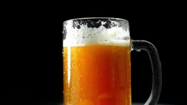 hrnek čerstvého studeného piva s pěnou izolovanou na černém