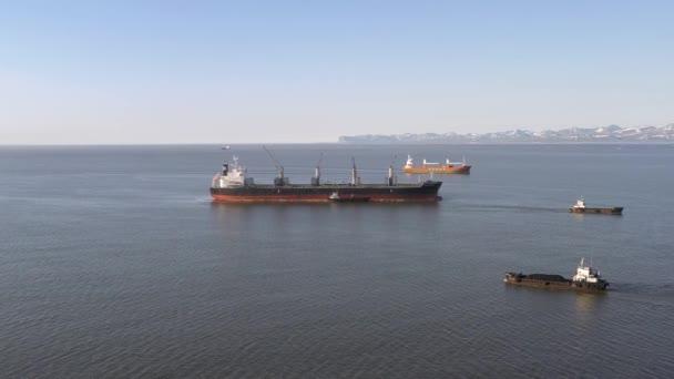 Beringovskiy, region Chukotski, Rusko - 22. června 2019: Loď na přepravu volně loženého nákladu Bulk Aquila je naložena uhlím na kotvišti přístavu Beringovskiy. Střílí seshora. Poblíž nákladních člunů plují.