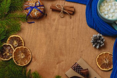 Christmas background with fir, scarf, dry orange, cone, biscuits, cinnamon
