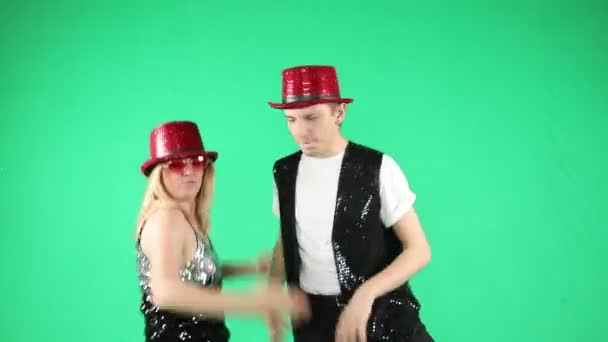 Active funny young couple dancing jumping and laughing with a funny gesture on green chroma key background. Video footage. Silly crazy happy mood